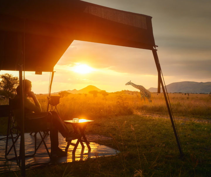 Woman rests after safari in luxury tent during sunset